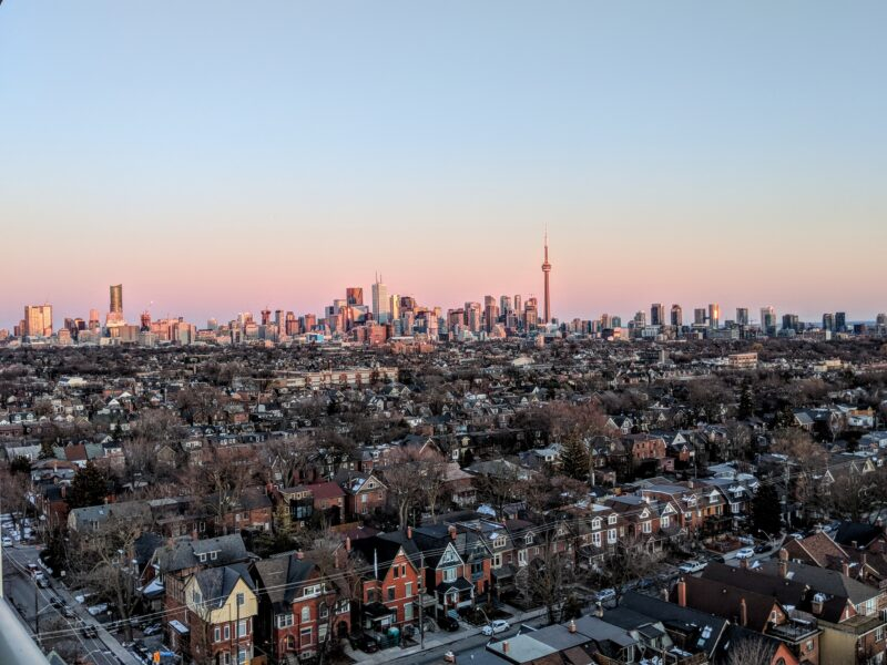 Aerial shot of the city of Toronto with a neighbourhood in the foreground.