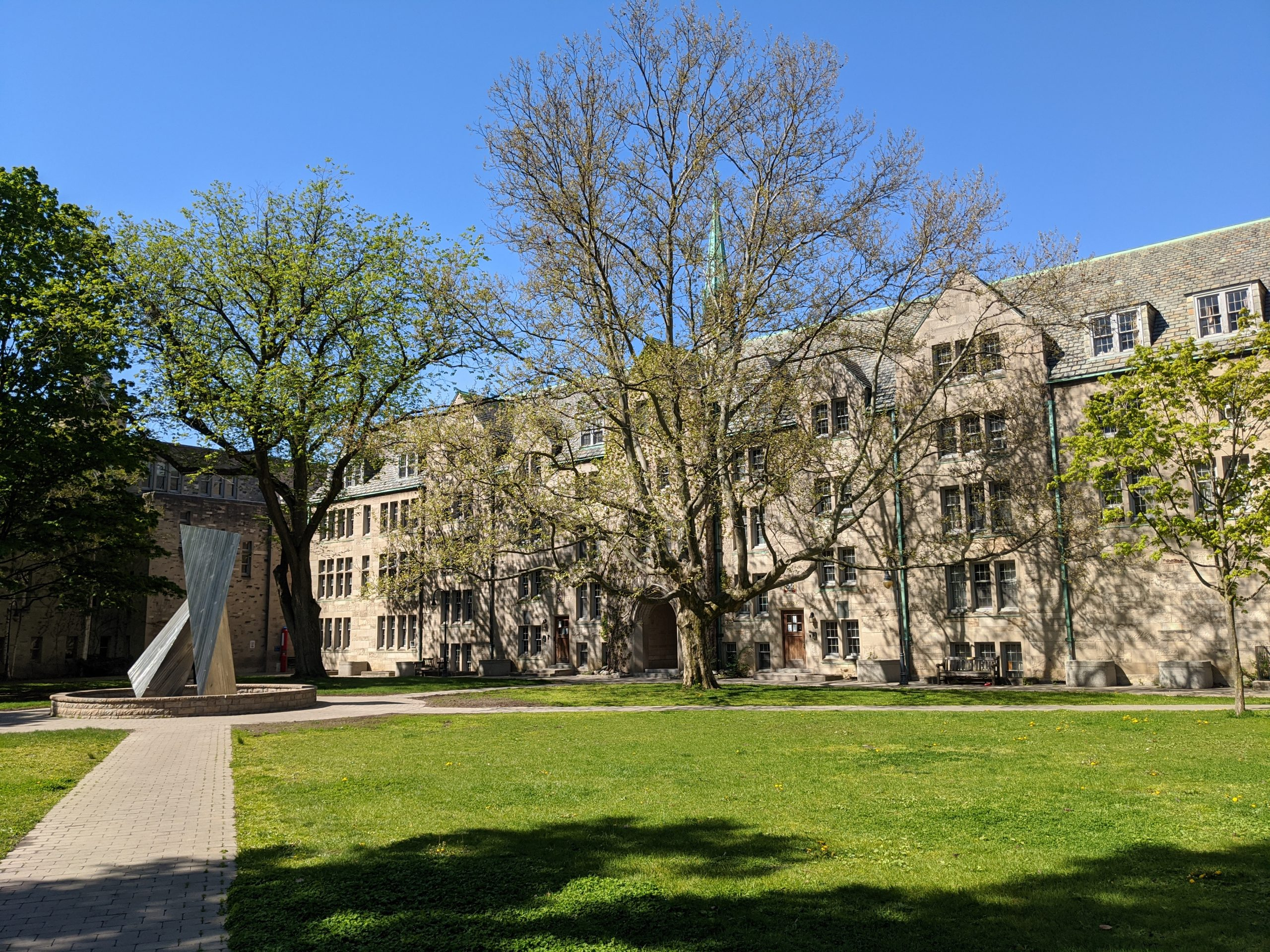 Sunny image of the St. Mike's quad and sculpture, with a vibrant green lawn and blue sky and the trees starting to bud