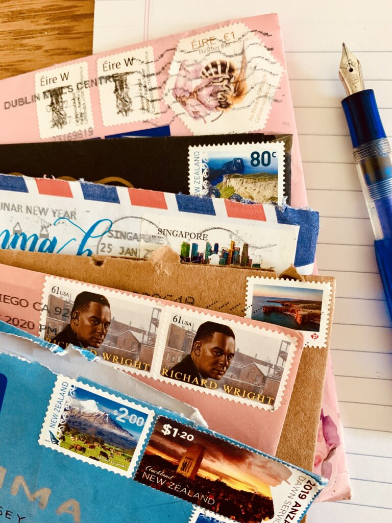 Close focus photograph of six envelopes resting on a pad of paper next to a fountain pen. The envelopes have stamps from Ireland, New Zealand, Singapore, Canada, and USA.