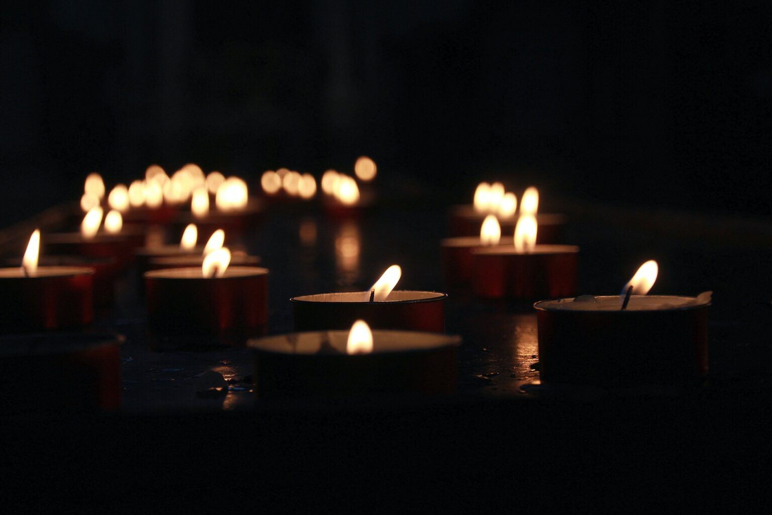 Photograph of multiple tea light candles floating on a dark body of water at night. There are many more candle flames out of focus in the background.