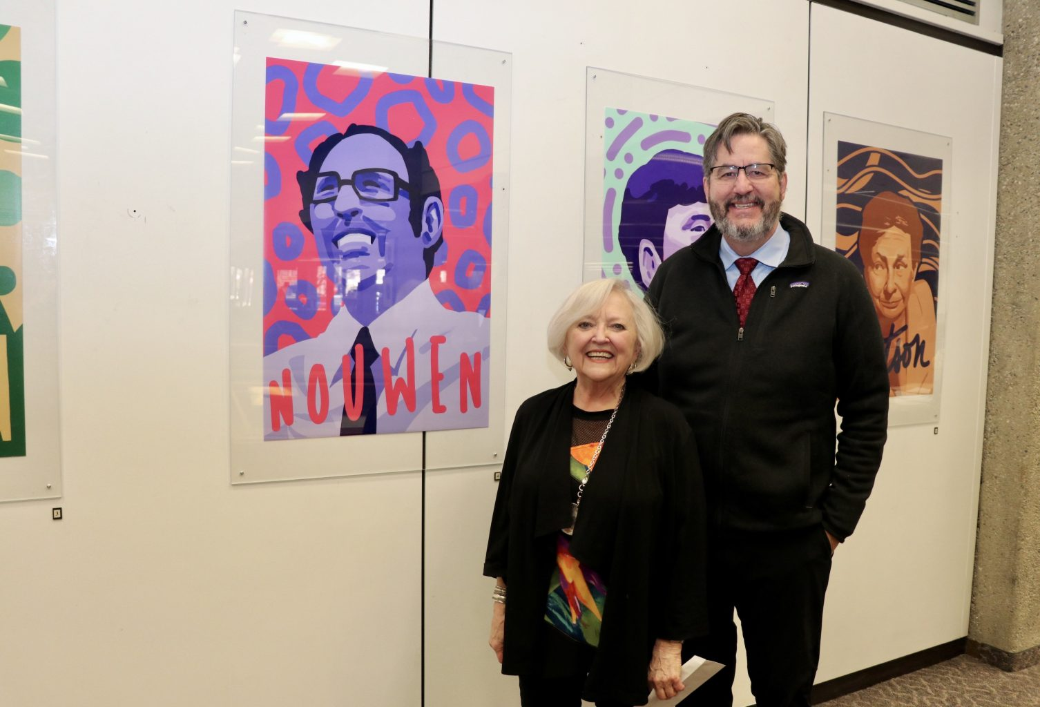 Photograph of Karen Pascal and David Sylvester, smiling, in front of an illustration of Henri Nouwen on a Kelly Library wall.