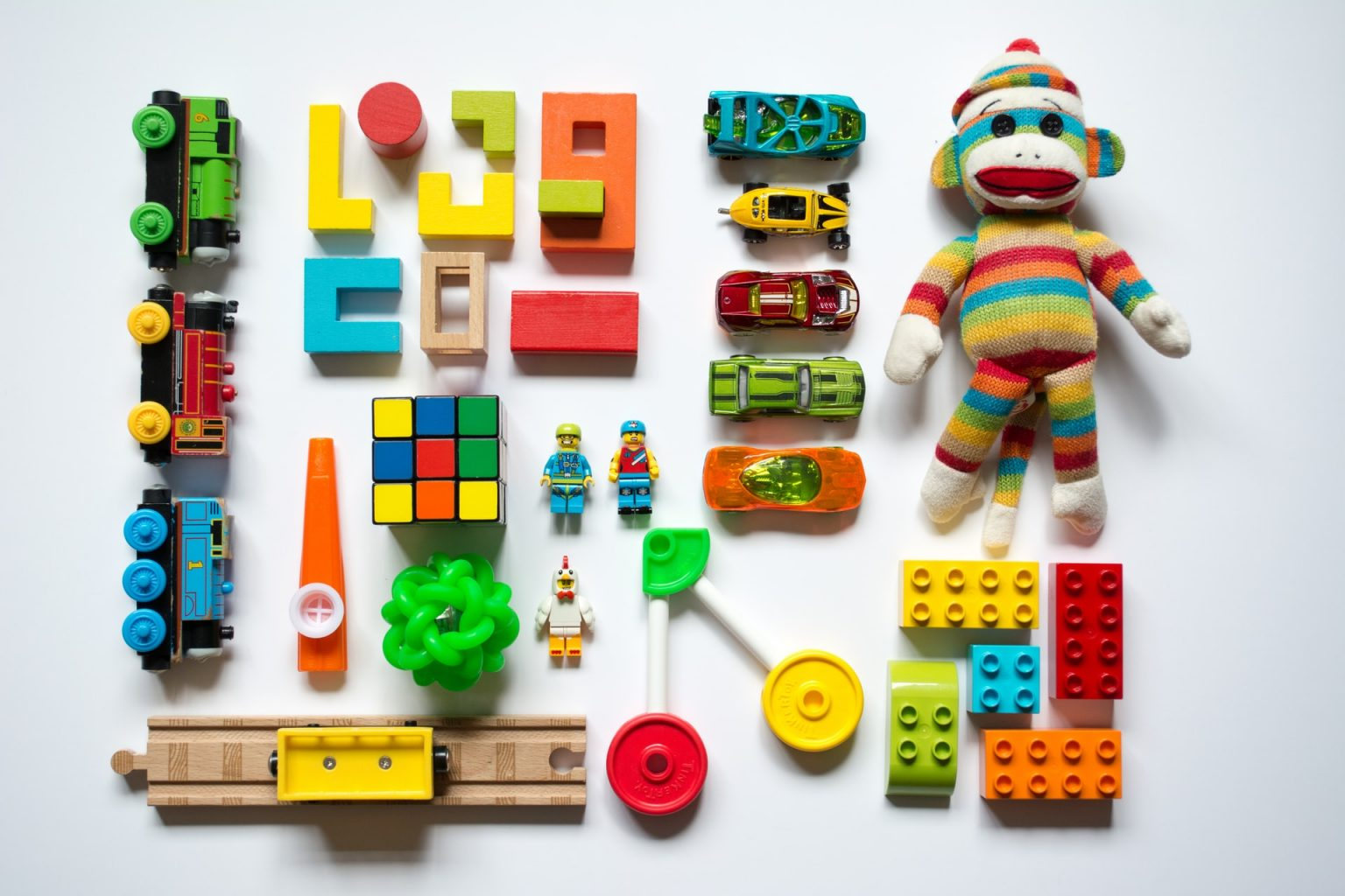 Still life photograph of a white background laid out with multiple brightly coloured children's toys: Thomas trains, a train track, blocks, a Rubik's cube, a kazoo, a bouncing ball, Lego figures, Hot Wheels, a striped sock monkey, Lego blocks, and connecting toys.