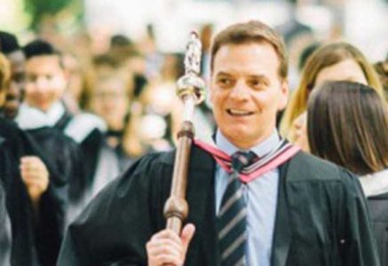 Duane Rendle in academic regalia carrying a ceremonial mace at the head of an outdoor academic procession