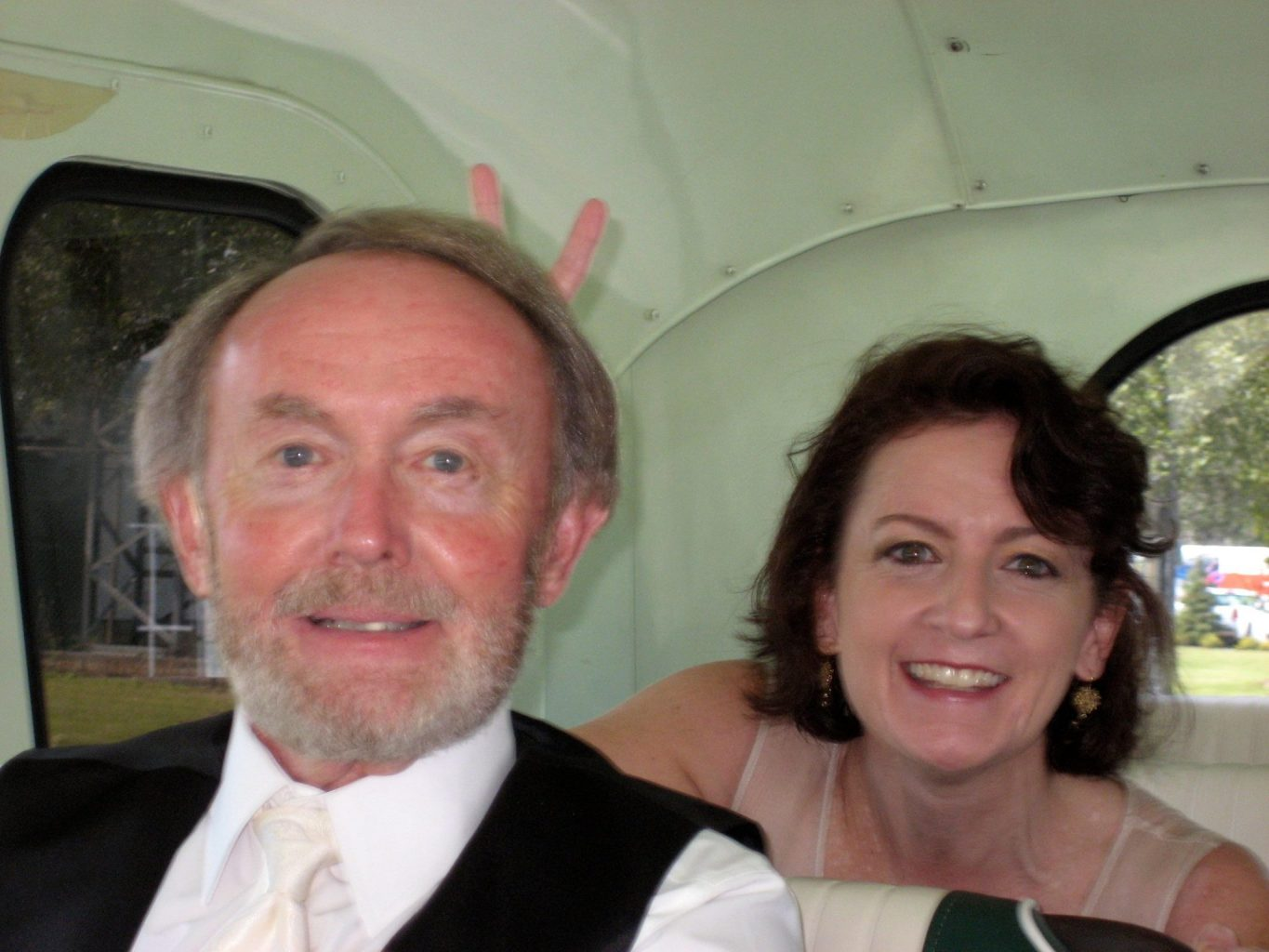 """Photograph of Laurie Morris and her father sitting in formal wear in the back of a vehicle. Laurie is doing """"bunny ears"""" behind her dad's head."""
