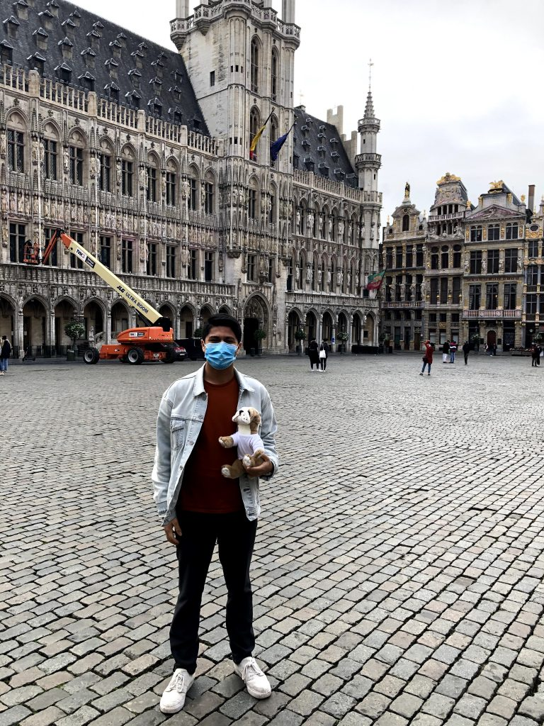 Photograph of post author Nicolas Vergara Ruiz standing in front of The Grand Place, the central square of Brussels, Belgium, wearing a blue medical mask and holding a Basil the bulldog plushie.
