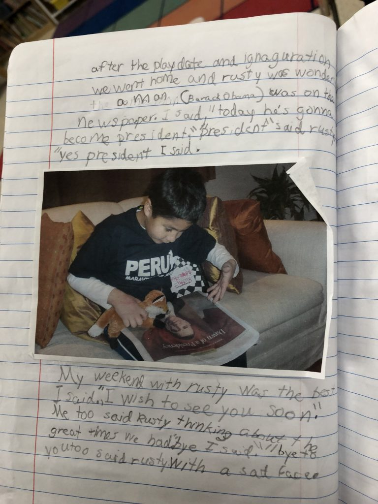 """Photograph of a lined notebook with writing and a photograph of a young Nicolas Vergara Ruiz wearing a shirt that says """"PERU"""" and holding a plush fox to a photograph of Barack Obama in a newspaper.   The writing: """"A man (Barack Obama) was on the newspaper. I said, 'today he's gonna become president.' 'President' said Rusty 'yes president' I said.   """"My weekend with Rusty was the best I said. 'I wish to see you soon.' Me to said Rusty thinking about the great times we had. 'Bye' I said. 'Bye to you too' said rusty with a sad face."""